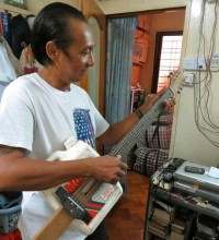 Former Political Prisoner Win Maw plays a guitar he made in prison