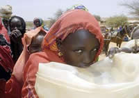 Ten-year-old Nadifa Isadurgi drinks clean water pumped from a source within Touloum camp in the Darfur region of Sudan.
