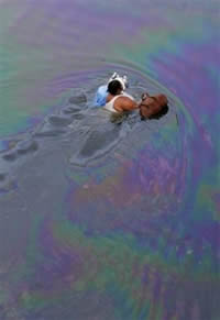 Resident of New Orleans, swimming in oil-slicked water.